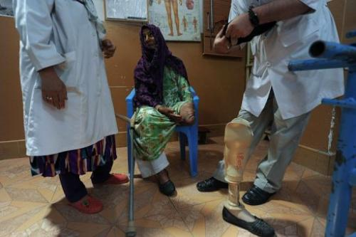 Afghan doctors in the city of Mazar-i-Sharif on May 23, 2012 with a woman who lost her leg from a landmine blast