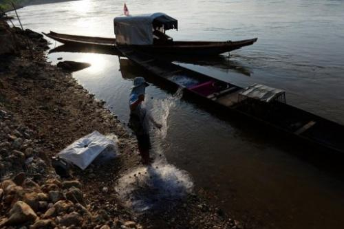 A fisherman stands on the bank of the Mekong river as he checks his net, in Wiang Kaen, on May 29, 2013