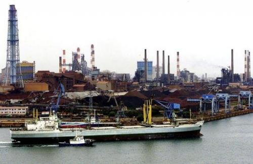 A freighter arrives at Kashima's main port with a metal factory seen in the background, on June  1, 2001