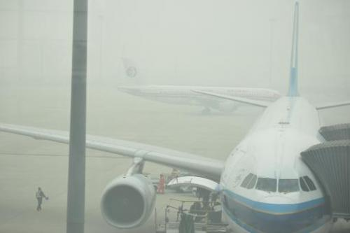 Aircraft are barely visible through thick smog on the tarmac of Hongqiao airport in Shanghai as severe pollution blankets the ci