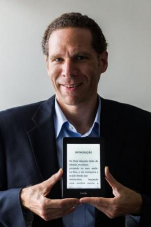 Alex Szapiro, head of Amazon Brasil, poses with a Kindle reader after an interview with AFP in Sao Paulo, March 15, 2013