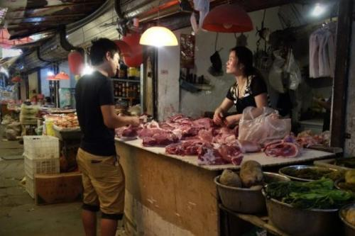 A man browses meat at a shop selling pork in Beijing on June 1, 2013