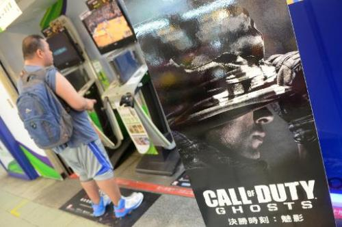"A man plays video games next to a sign advertising the videogame ""Call of Duty"" in Taipei on November 5, 2013"