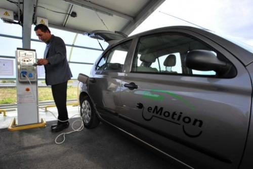 A man plugs an electric powered car to a charging station in Sofia on October 17, 2012