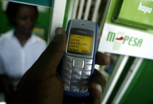 A man sends money through a mobile phone money service called M-PESA in Kenya's capital Nairobi on April 23, 2007