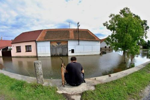 A man sits at a flooded street in Putim, near Pisek, Czech Republic, on June 5, 2013
