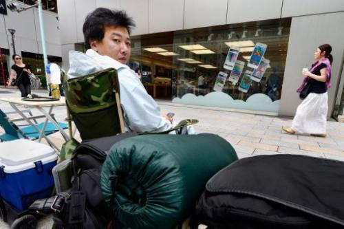 A man sits outside a Tokyo Apple Store on September 11, 2013, ready to buy the new iPhone 5s, out on September 20