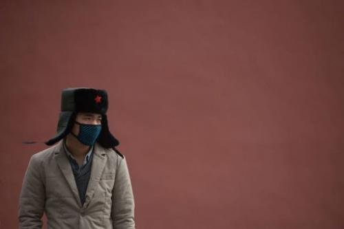 A man stands before a wall inside the Forbidden City during heavy pollution in Beijing on February 28, 2013