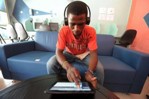 A man uses a tablet computer in the world's first tablet cafe, in Dakar, on May 28, 2013
