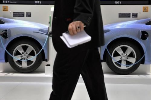 A man walks past a wall showing the electric car system at the French carmaker Renault's booth on March 2, 2011