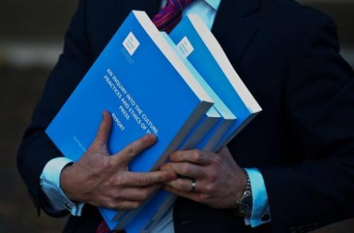 A member of the press holds copies of the Leveson Inquiry into press standards in London, on November 29, 2012