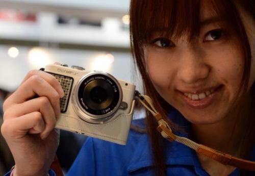 A model poses with a digital camera during the photo imaging show in Yokohama, Japan, on January 31, 2013