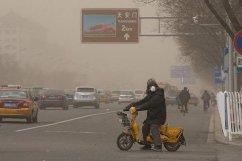 A motorist wearing a face mask waits to cross a road in heavily polluted Beijing on February 28, 2013