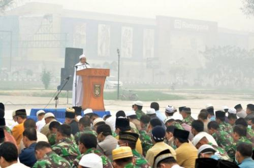 A Muslim cleric leads Indonesian officials and residents in mass prayers, in Dumai, on June 25, 2013