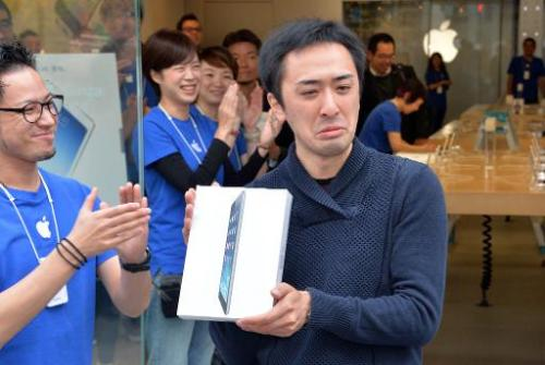 An Apple store's first customer of the day shows off his iPad Air tablet in Tokyo on November 1, 2013
