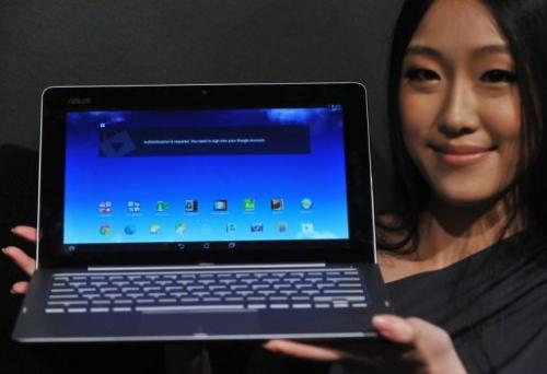 "An Asus employee displays the ""Transformer Book Trio"" during a press conference in Taipei, on June 3, 2013"