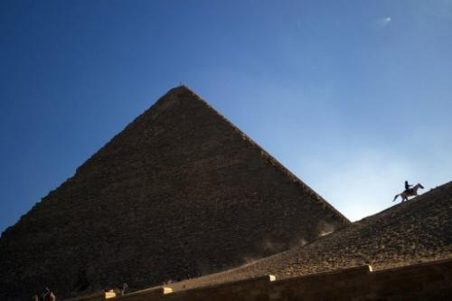 An Egyptian man rides a horse past one of the three Giza pyramids, south of Cairo, on December 22, 2012