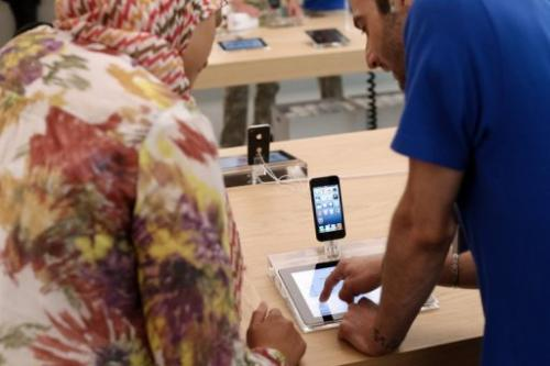 An employee and a customer look at Apple's iPhone 5 smartphones and iPad on July 6, 2013 in Rosny-sous-Bois, near Paris.