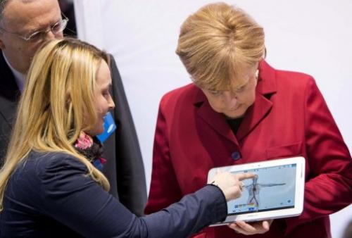 An employee demonstrates a Samsung tablet to Germany's Angela Merkel (R) at the CeBIT show in Hanover on March 5, 2013