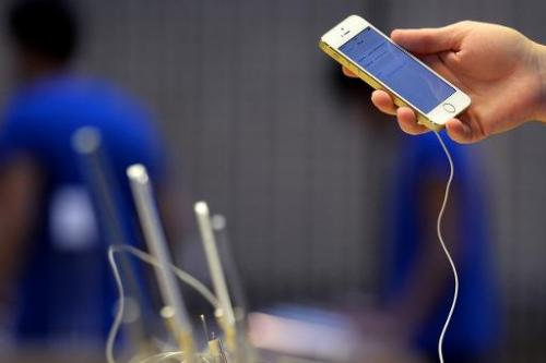 An employee prepares a display iPhone 5s at the Apple store, in central London, on September 20, 2013