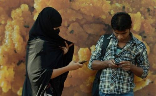 An Indian woman checks her mobile as she walks past a bystander in Mumbai, on February 20, 2013