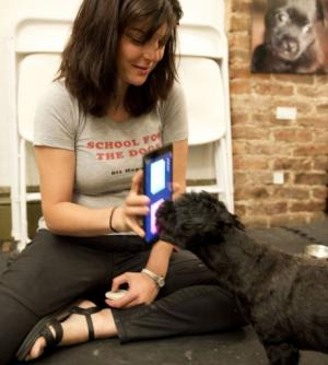 Anna Grossman holds her Ipad while her dog Amos touches the screen with his nose August 19, 2013 in New York