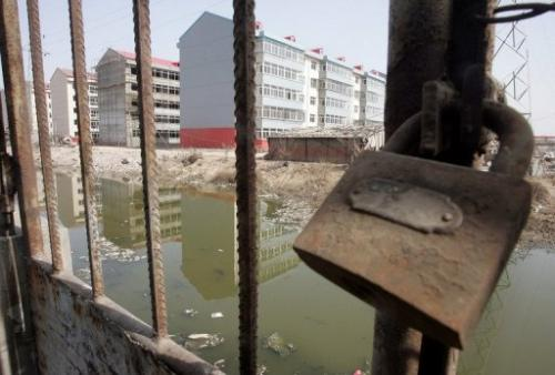 A padlock secures a gate leading to a polluted river once used for swimming, in Liukuaizhuang Village in Tianjin.