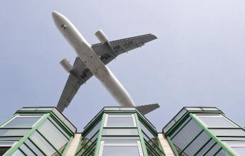 A passenger jet flies over a commercial building as it prepares to land at Berlin's Tegel airport, on March 27, 2012
