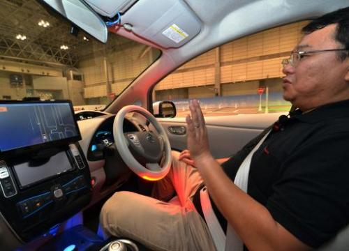 A passenger sits in Nissan's new self-driving car at the CEATEC preview in Chiba on September 30, 2013