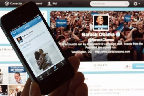 A person poses with a cell phone in front of a computer screen to check Barack Obama's tweet on November 7, 2012, Paris