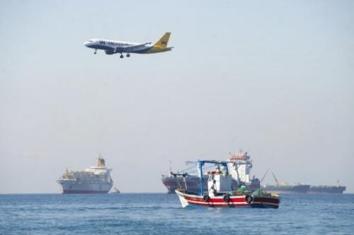 A plane flies over men from La Linea de La Concepcion fishing on August 16, 2013 near Gibraltar