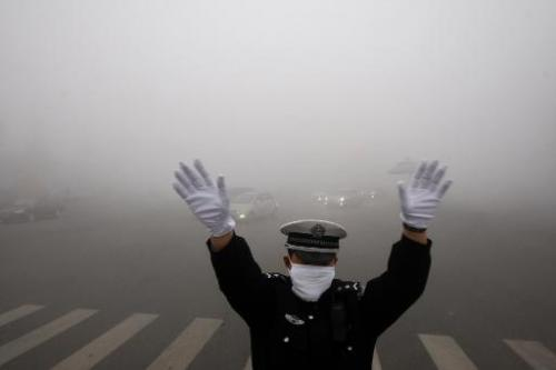 A policeman directs traffic in heavy smog in Harbin, China's Heilongjiang province, on October 21, 2013
