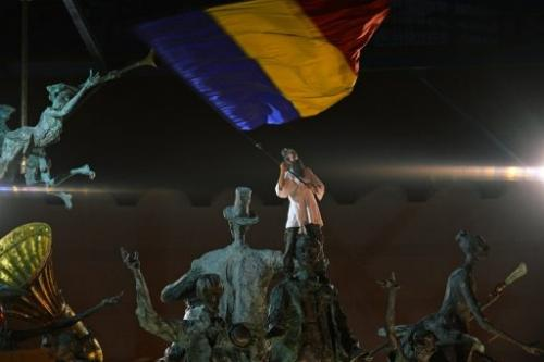 A protester waves a Romanian flag on a monument during anti-mining demonstrations in Bucharest, September 15, 2013