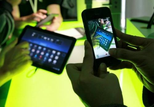 A reporter uses a cell phone to take a photograph of Google Android 3.0 Honeycomb OS on February 2, 2011 in California