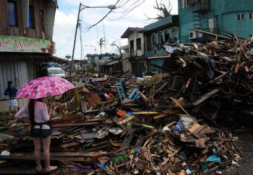 A resident stands amongst a pile of debris washed inland along a road in Tacloban, Leyte province, central Philippines on Novemb