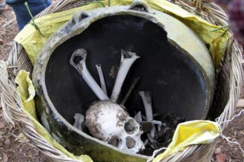 A skull and bones in broken jars in a remote Cambodian jungle, on January 7, 2013