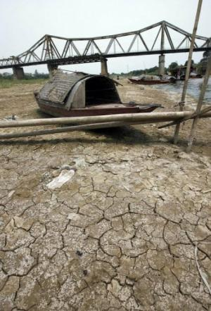 A small boat lies on the bed of the Red River as it has been hit by drought near Hanoi, on April 19, 2007