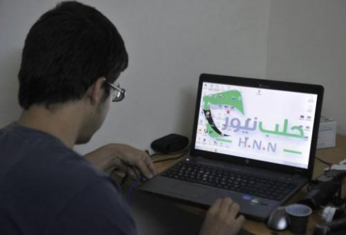 A technician, looks at a laptop at a news station in the northern Syrian city of Aleppo on October 7, 2012