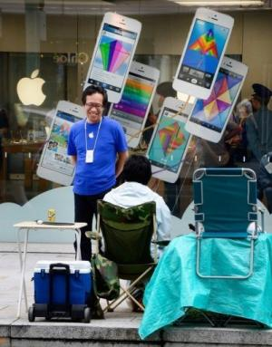 A Tokyo Apple store staff member chats with a man queuing to buy the iPhone, pictured September 11, 2013