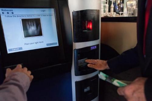 A user tries out the world's first bitcoin ATM at Waves Coffee House on October 29, 2013 in Vancouver, British Columbia