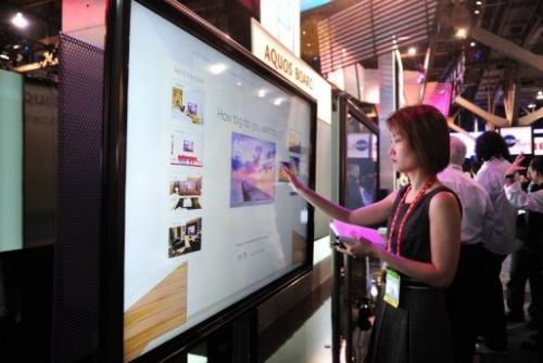 A visitor checks out a Sharp's touch screen TV set at an electronics show in Las Vegas, Nevada, on January 10, 2012