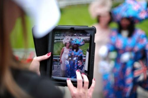 A woman at Ascot race course on June 20, 2013, photographs two other racegoers on a tablet computer