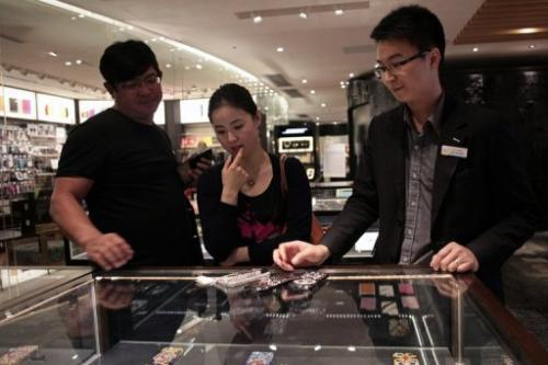 A woman inspects custom-built iPhone cases in Hong Kong on April 23, 2013.