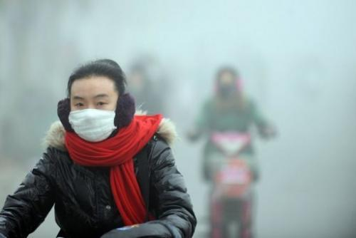 A woman rides a bike in heavy smog in Haozhou, central China's Anhui province on January 30, 2013