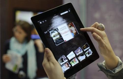 A woman tries out an e-book reader app on an Apple iPad at the Leipzig Book Fair on March 15, 2012
