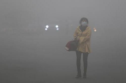 A woman wearing a face mask walks in heavy smog in Harbin, China's Heilongjiang province, on October 21, 2013