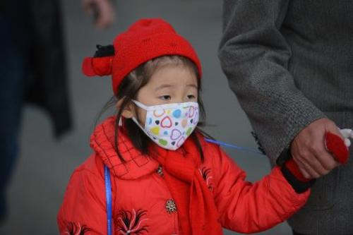 A young girl wears a face mask on a street in downtown Shanghai as severe pollution hits the city on December 5, 2013