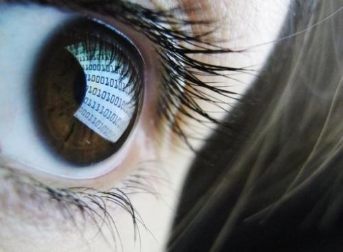 Binary code is reflected from a computer screen on a woman's eye