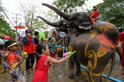 Children take part in water battles with elephants in Ayutthaya province on April 12, 2013 during the Songkran Festival