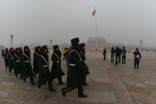 Chinese military police march through Tiananmen Square blanketed in pollution in Beijing on January 30, 2013
